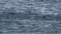 Athletes compete in the ocean swimming part of a triathlon. Stock Footage