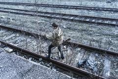 Young boy walking on railroad tracks Stock Photos