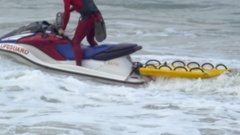 A surf rescue lifeguard rides on a personal watercraft jetski. Stock Footage