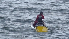 A surf rescue lifeguard performs a rescue on a personal watercraft jetski. Stock Footage