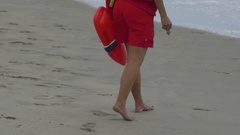 A beach lifeguard holds her red rescue can. Stock Footage