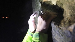 Detail of a man's hands as he climbs boulders at night. Stock Footage
