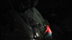 A young man climbs boulders at night while bouldering. Stock Footage