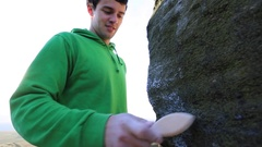 A young man brushes chalk of boulders while bouldering. Stock Footage