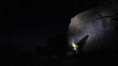 A young man climbs boulders at night while bouldering, time-lapse. Stock Footage