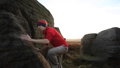 A young man climbs boulders while bouldering. Stock Footage