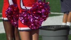 Detail of high school cheerleaders cheering with their pom-poms at a football ga Arkistovideo