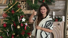 Pretty woman showing thumbs up after decoration of christmas tree HD Stock Footage