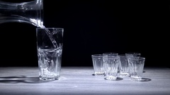 Water pouring in big glass with empty small glasses on the side. Stock Footage