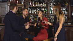 Two young couples in club or bar having fun, toasting wine glasses Stock Footage