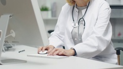 In the Doctor's Office. Mid Adult Female Doctor Works at Her Desktop Computer.  Stock Footage