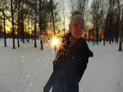 Girl look from behind burning sparkler, slow motion shot at winter park Stock Footage