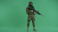 Serviceman standing with weapon and looking at side at green screen Stock Footage