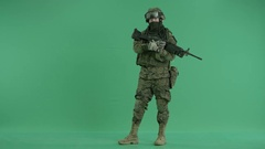 Serviceman standing with weapon and looking at camera at green screen Stock Footage
