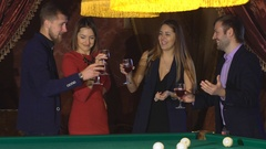 Two couples talking near the pool table and drink Stock Footage