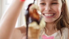Caucasian girl pouring chocolate syrup over ice cream cone Stock Footage