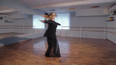 A woman in an empty studio takes dance lessons. This is her hobby. She rehearses Stock Footage