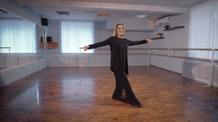 Beautiful white-haired woman in silk black suit dancing in classroom with ballet Stock Footage