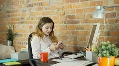Female assistant texting on smartphone during her break in the office Stock Footage