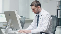 Male Doctor is Working at His Desk. He Uses Personal Computer Stock Footage