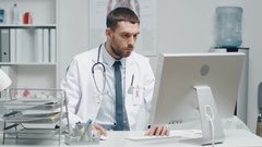 Close-up of a Male Doctor is Working at His Desk. He Uses Personal Computer Stock Footage