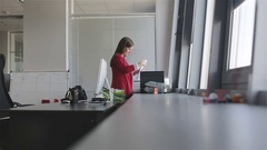 Beautiful woman in red jacket works in the office. Stock Footage