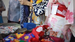 Sellers dressed in Japanese traditional clothing selling fabric for kimonos Stock Footage