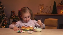 Girl smears cream on cinnamon rolls Stock Footage