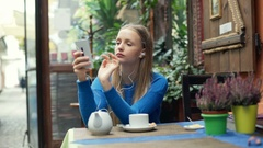 Morose girl plays music on smartphone and looking thoughtful Stock Footage
