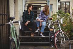 Couple sitting on stairs and interacting Stock Photos