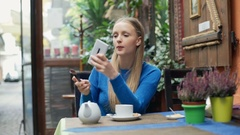 Pretty, blonde girl putting blush on her cheeks and using smartphone as a mirror Stock Footage