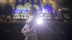 Brunette woman in lilac costume dances belly dance in front of bar Stock Footage