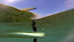 Above and below detail shot of the fin on a longboard surfboard, slow motion. Stock Footage