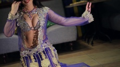Brunette woman in lilac costume dances belly dance on floor Stock Footage