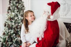 Dream is real in christmastime. happy little cute girl sitting on the lap of Stock Photos