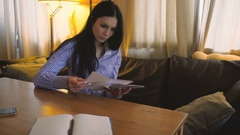 Young brunette sits in her Office and looking at records in paper sheets Stock Footage
