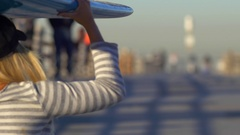 A young woman longboard skateboarding while balancing a surfboard on her head. Stock Footage