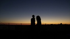 Silhouette couple playing scenario at sunset Stock Footage