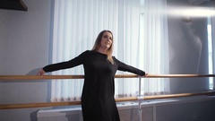 Beautiful female ballet dancer in silk black suit standing near ballet barre in Stock Footage