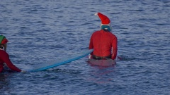 Santa and Mrs. Claus sit on their surfboards waiting for waves while surfing. Stock Footage