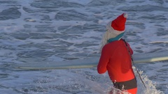 Santa Claus paddles out on his knees to go surfing. Stock Footage