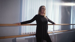 Beautiful housewife makes a workout before dancing at the ballet barre in a Stock Footage