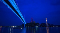 The Bai Chay Bridge in Ha Long, Vietnam lit up with colorful lighting at night. Stock Footage