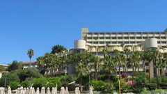 Contemporary hotel decorated with palms near the ocean, luxury vacation resort Stock Footage