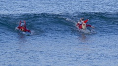 Santa and Mrs Claus ride a wave surfing at the beach. Stock Footage
