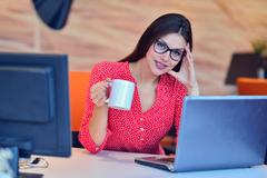 Beautiful classy brown haired businesswoman enjoying coffee in bright office Stock Photos
