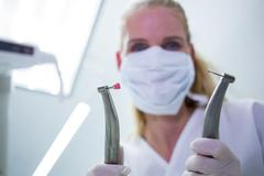 Female dentist with surgical mask holding dental instruments Stock Photos