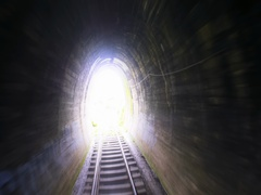 Abstract video of fast moving camera through old railway tunnel toward light Stock Footage