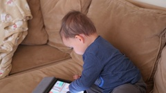 A little boy toddler plays on a ipad on couch Stock Footage