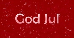 "Merry Christmas text in Norwegian ""God Jul"" turns to dust from bottom on red Stock Footage"